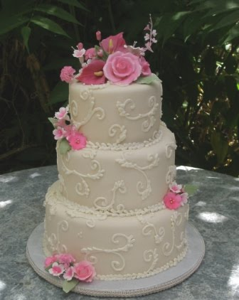 Three tier white wedding cake with gorgeous pink roses sugar calla lilies
