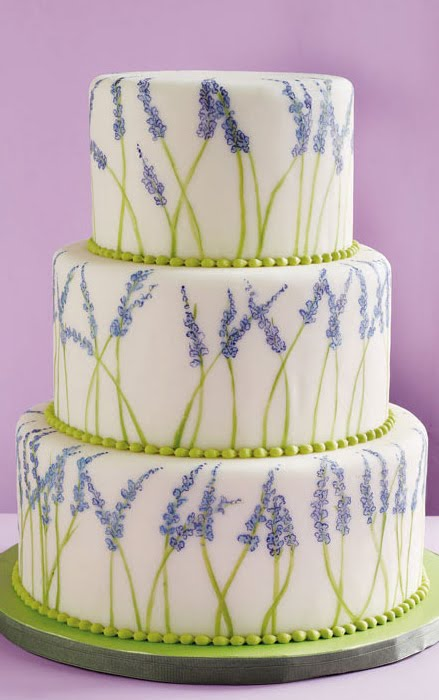 Three tier white round wedding cake decorated with lavender flowers