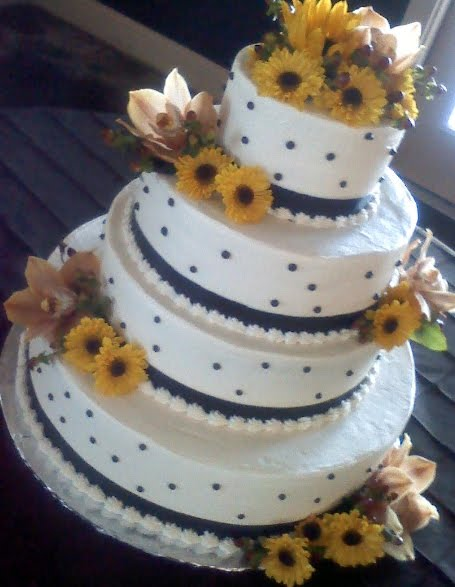 Yellow and white polka dot and stripes wedding cake with sunflower cake