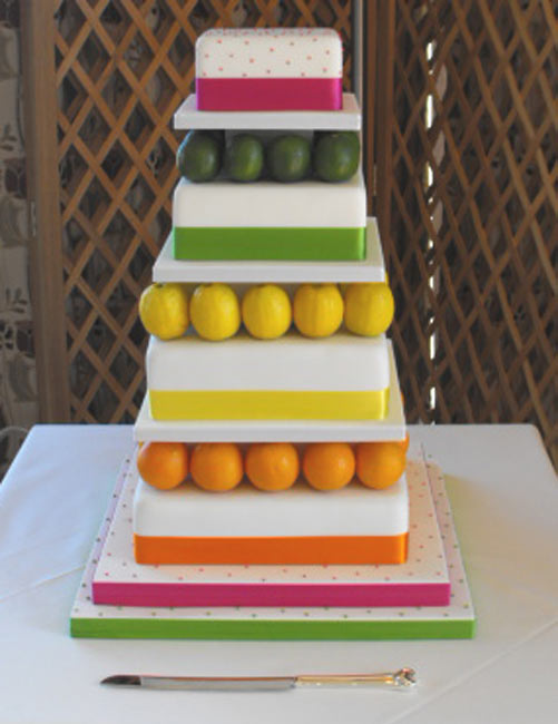 A true rainbow wedding cake made up of 6 round tiers each tier is iced in