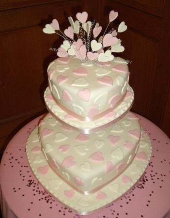 White and pink two tier wedding cake with heart pattern and heart cake
