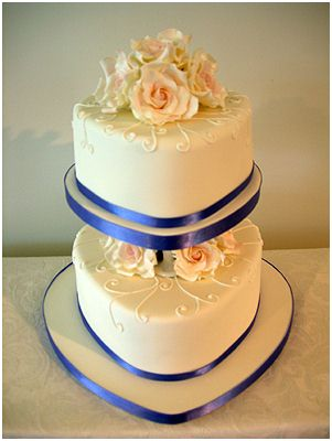 Two tier heart wedding cake with peach colored sugar roses and deep blue