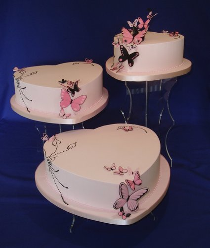 Three tier white wedding cake with multi hued pink sugar butterflies.