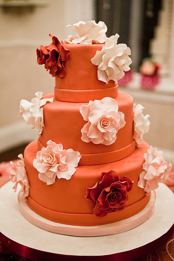 Three tier deep orange round wedding cake with white flowers and a white
