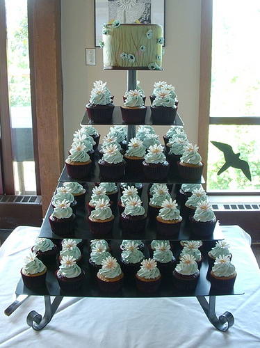 Square shaped cupcake tower set over four lovely tiers with a mini cake to