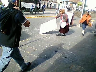 Letrero tirado por el viento y siendo recogido por una mujer