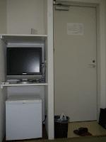 【照片:從房內照向門口。房內有電視機和冰箱,櫃子上還有小鏡子,電視跟冰箱旁都有二孔電源插座,右下那包就是旅館免費出借的衣物。】