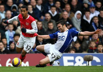 Theo Walcott of Arsenal skips past a challenge from Damien Johnson of Birmingham City