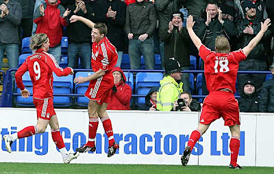 Liverpool midfielder Steven Gerrard (center) celebrates after his shot went in off Bolton goalkeeper Jussi Jaaskelainen. Gerrard's attempt appeared to be going wide but the ball rebounded off the goalkeeper and crossed the line.