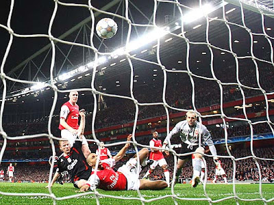 Dirk Kuyt of Liverpool (L) beats Gael Clichy and Manuel Almunia of Arsenal to score