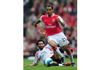 Theo Walcott of Arsenal rides a tackle by Jermaine Pennant of Liverpool