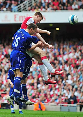 Nicklas Bendtner of Arsenal rises above Phil Jagielka of Everton to score a goal.