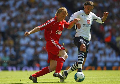 Dimitar Berbatov of Tottenham Hotspur is challenged by Dirk Kuyt of Liverpool
