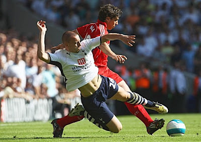 Alan Hutton of Tottenham Hotspur tackles Emiliano Insua of Liverpool.