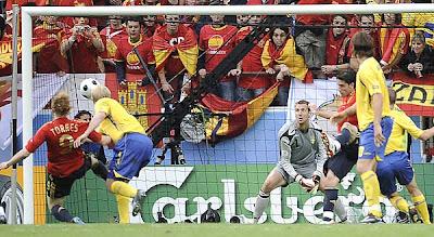 Spain's Fernando Torres, left, scores the opening goal against Sweden.