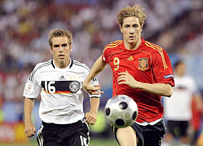 Spanish forward Fernando Torres (right) runs for the ball ahead of German defender Philipp Lahm.