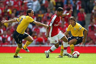 Denilson of Arsenal (center) battles for the ball with Marek Cech of West Bromwich Albion and Jonathan Greening of West Bromwich Albion (left). Arsenal won the game 1-0.
