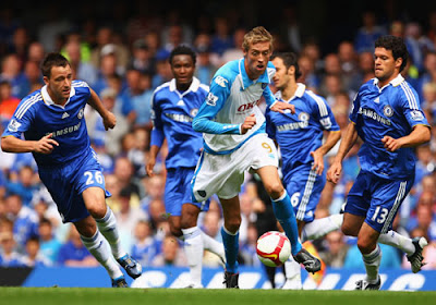 Peter Crouch (center) of Portsmouth is watched by John Terry (left) and Michael Ballack (right) of Chelsea during their Premier League match at Stamford Bridge on August 17, 2008 in London, England.