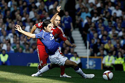 Everton midfielder Mikel Arteta (left) turns away from the attentions of Liverpool defender Andrea Dossena.