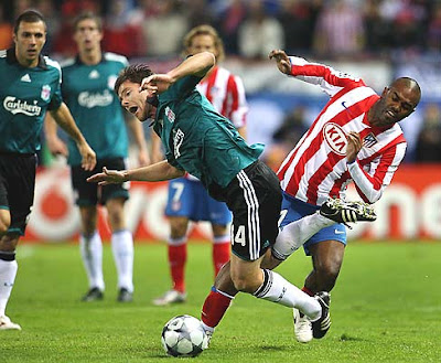 Xabi Alonso (L) of Liverpool is fouled by Florent Sinama Pongolle of Atletico Madrid