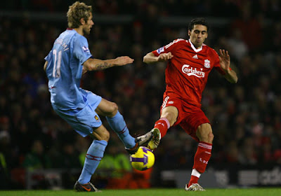 Alvaro Arbeloa of Liverpool competes for the ball with Valin Behrami of West Ham United