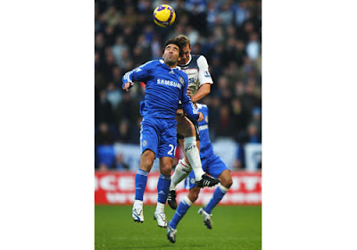 Deco of Chelsea and Kevin Davies of Bolton Wanderers go up for a header