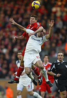 Steven Gerrard of Liverpool goes up for a header with Gavin McCann of Bolton Wanderers during their Barclays Premier League match at Anfield in Liverpool, England.