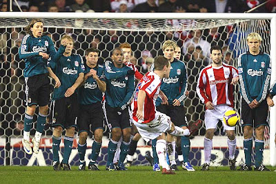 Glenn Whelan of Stoke City fires in a free kick towards the Liverpool wall.