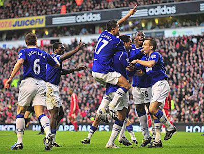 Joleon Lescott of Everton celebrates with teammates after scoring against Liverpool.