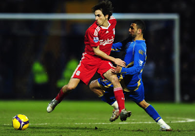 Yossi Benayoun of Liverpool is confronted by Nadir Belhadj of Portsmouth