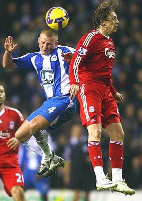 Lee Cattermole of Wigan jumps with Lucas Leiva of Liverpool during their Barclays Premier League match at the JJB Stadium in Wigan, England.<br />
