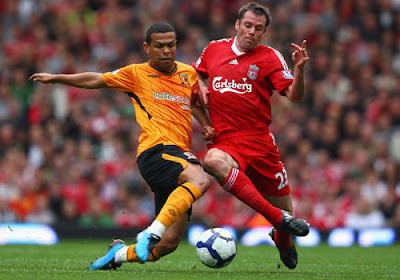 Jamie Carragher of Liverpool battles for the ball with Geovanni of Hull City