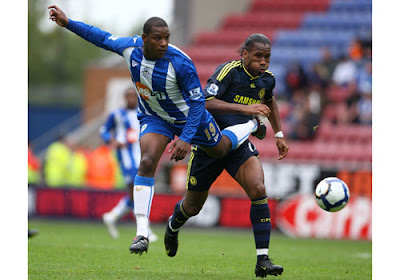 Titus Bramble of Wigan Athletic gets to the ball ahead of Didier Drogba