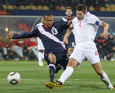 Steven Gerrard of England shoots and scores under pressure from Ricardo Clark of the United States during the 2010 FIFA World Cup South Africa Group C match between England and USA at the Royal Bafokeng Stadium on June 12, 2010 in Rustenburg, South Africa.