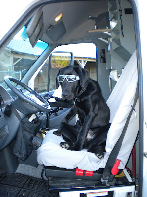 Dagan in a pair of safety glasses, sitting in the driver's seat of the Fire King Sprinter