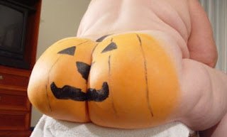A giant naked butt with a pumpkin painted on it