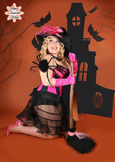 1950s style pin-up image of a blond model in front of a haunted house backdrop with a giant spider on her arm