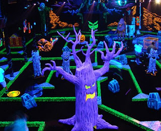scary glow in the dark trees scattered around a monster-themed miniature golf course