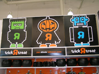 Photo of a Frankenstein pumkinhead and robot graphics hanging in a Toys R Us Store at Halloween