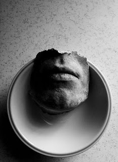 a small dismembered portion of a man's face sitting neatly on a white dinner plate