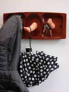 baby doll arms and legs being used as wall hooks to hold coats umbrellas and keys