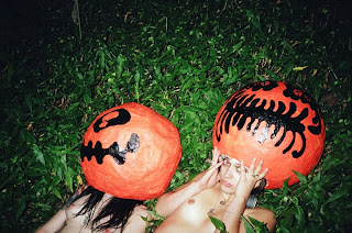 Topless models laying on the grass while wearing paper-mache pumpkins on their heads