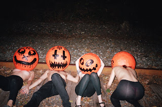 Topless models wearing paper-mache pumpkins on their heads