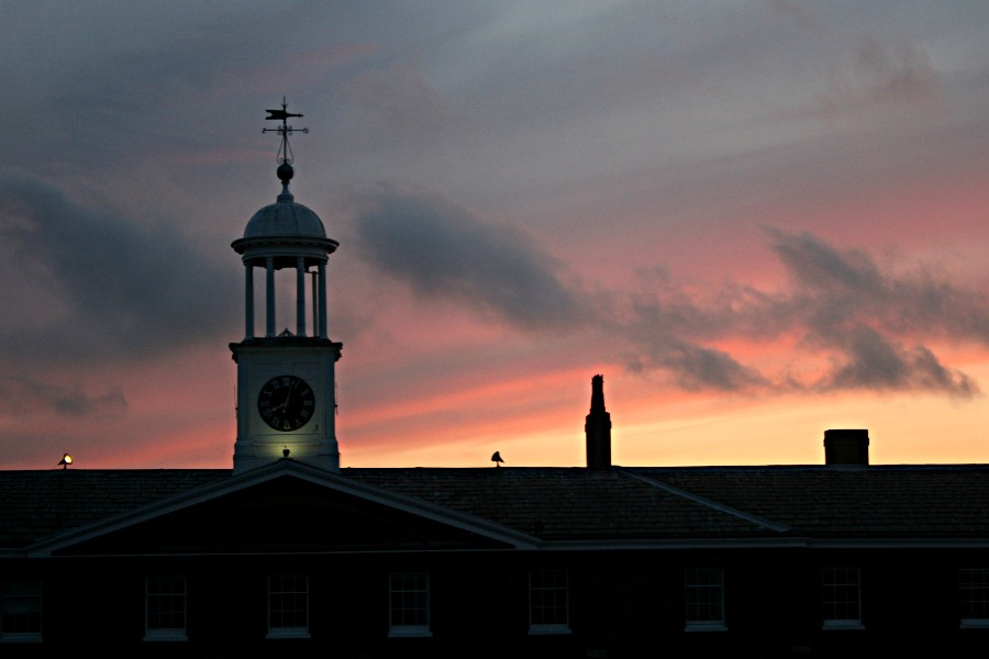 Admiralty Mews clock tower with a pink sunset