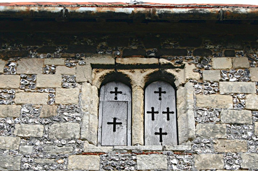 church window with wooden shutters with cut out crosses