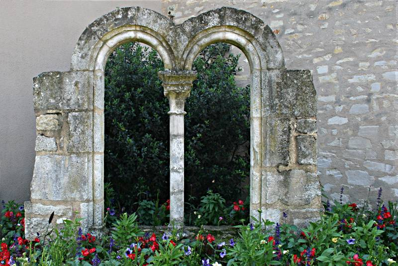 stone window openings used as a background for flower bed