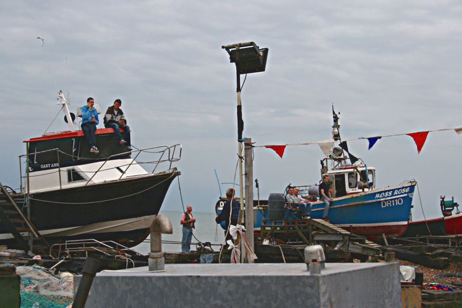 people sitting on beached fishing boats