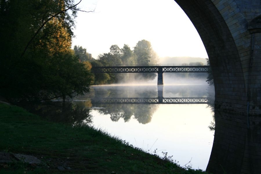 view of mist on river through bridge arch