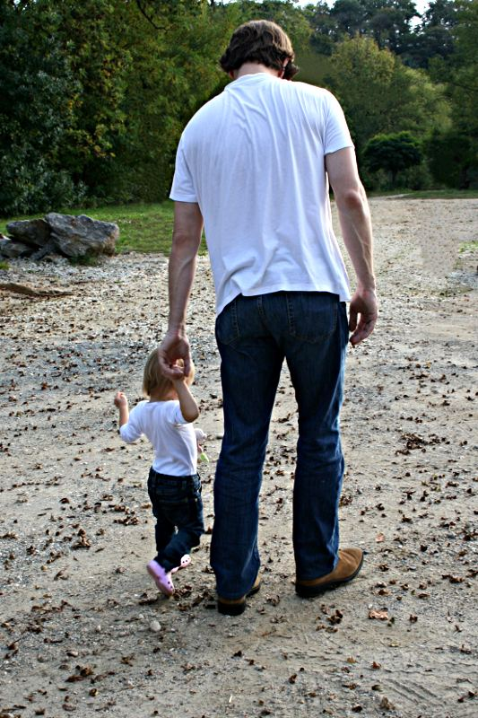 toddler and man walking hand in hand