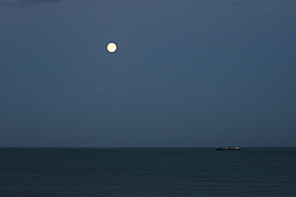 sea at twilight with ship and moon